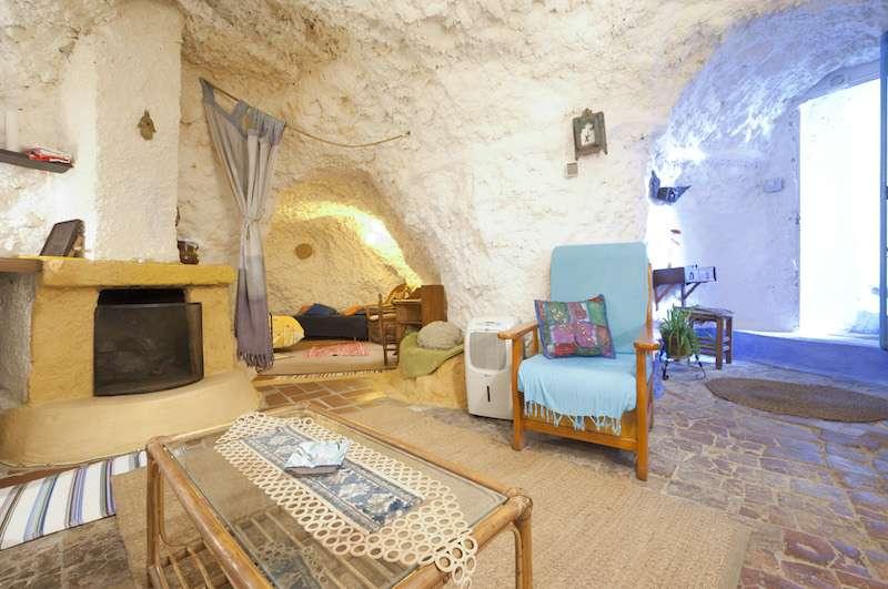 Casa Airbnb en una cueva con paredes blancas decorada con un sillón azul. Las cuevas-casa de Granada es una de las mejoras cosas que ver en Granada