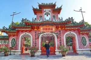 Templo pagoda en Hoian de color rosa con viajero con sombrero vietnamita