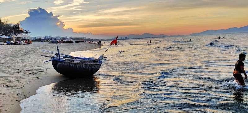 Qué ver en Hoian: playa de An Bang. Barca y niño en el mar al atardecer
