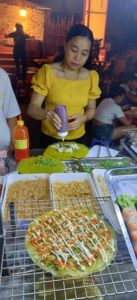 Comida callejera en Hoian. Mujer preparando una pizza vietnamita