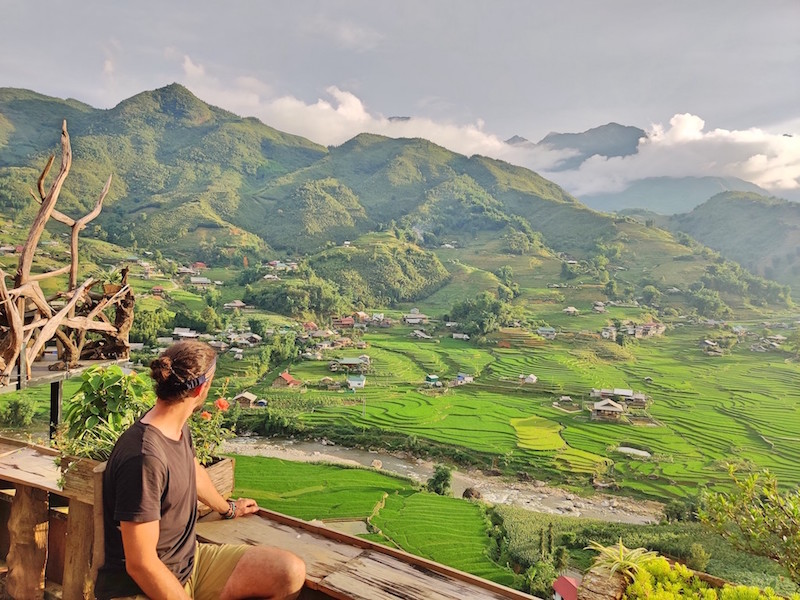 Viajero con camiseta negra posa en una terraza de un café en Vietnam. Las terrazas con vistas a campos de arroz y hacer trekking en Vietnam son las mejores cosas que hacer en Sapa