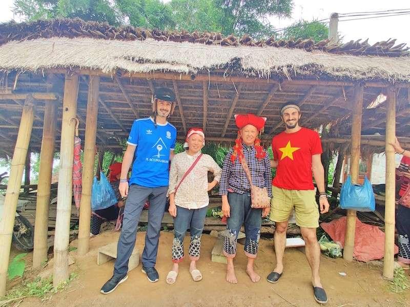 Viajeros y mujeres de la minoría étnica Hmong sonriendo con vestidos tradicionales. Visitar poblaciones con minorías étnicas es una de las mejores cosas que hacer en Sapa