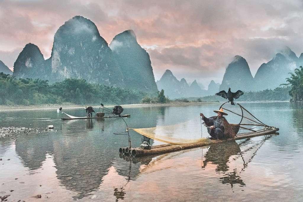 Pescador chino con red y balsa con pájaro sobre la cabeza y colinas de fondo. China es uno de los mejores países donde vivir con coronavirus