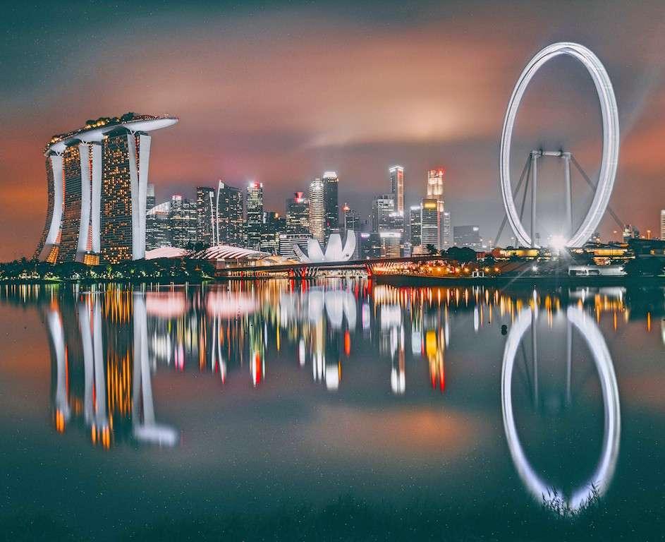 Marina Bay en Singapur con rascacielos y noria iluminados de noche con su reflejo sobre el mar. Singapur es uno de los mejores países donde vivir con coronavirus