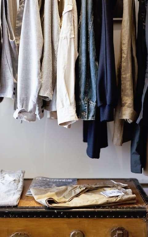 Ropa colgando y sobre una maleta. Elegir cuidadosamente la ropa antes de viajar es una de las mejores formas de cómo viajar con poco dinero