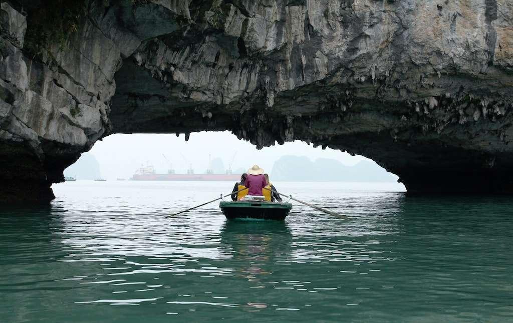Remero con sombrero típico vietnamita pasa por debajo de una formación rocosa en la bahía de Halong. Pasearse en barca es una de las mejores cosas que hacer en Halong Bay, Vietnam