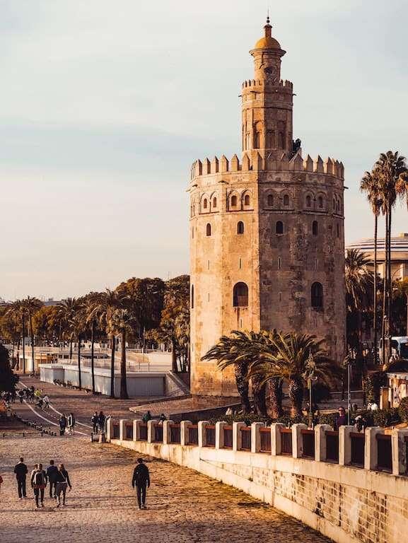 Torre del Oro circular de piedra junto a paseo en Sevilla