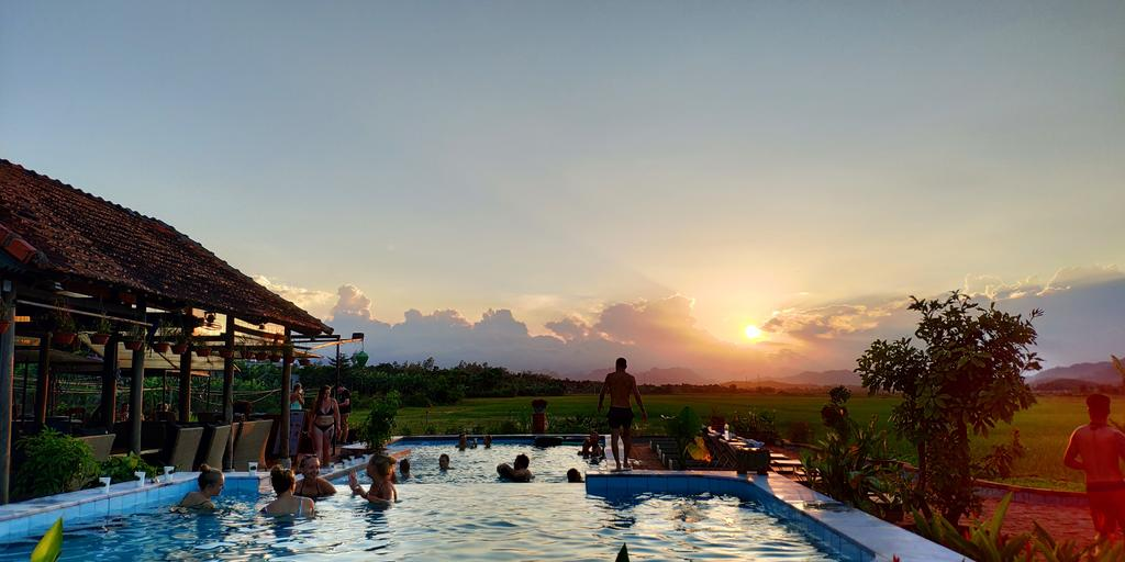 Turistas dentro de la piscina del hotel Farmstay en Vietnam. Este destino es conocido por tener cuevas en Phong Nha