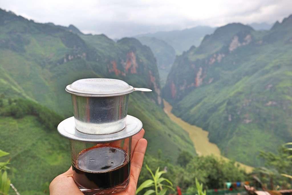 Café vietnamita con filtro sobre una mano enfrente del río del Ma Pi Leng Pass del viaje en moto por Vietnam del Ha Giang Loop
