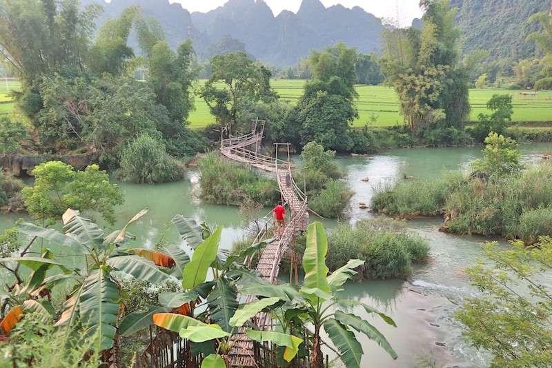 Viajero con camiseta roja camina sobre un puente de bambú entre paisajes verdes de campos de arroz y montañas. Se puede encontrar cerca de las cascadas de Ban Gioc en el Ha Giang Loop en Vietnam