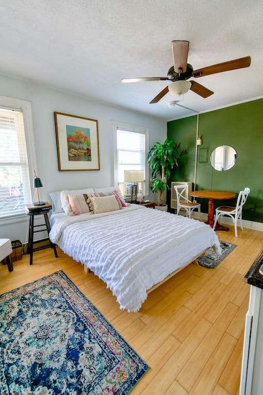 Cama con sábanas blancas en una habitación con pared verde y alfombra azul. Puedes dormir gratis en alojamientos como estos con mi código promocional Airbnb